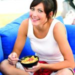A woman eats a salmon pokebowl on her couch