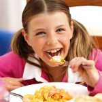 A little girl eats Scottish salmon pasta Label rouge