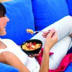 Eine Frau isst eine Lachsschale auf ihrer Couch.